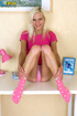 Juicy whore in a pink shirt, panties and socks does a blue dildo on a