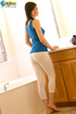 Welcoming damsel in a blue shirt and white leggings does a glass toy in