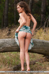 Stunning babe displays her sexy body as she sits on a big log wearing