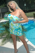 Blonde MILF in a light blue dress posing by the pool