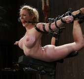 Bondage equipment keeps a gal's body bent in the…