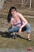 Bitch in a pink top and jeans smokes a fag and strips outdoors