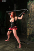 Stunning redhead gets gagged with a red ball and strapped on a metal cross