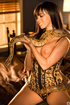 Brunette snake charmer in gold corset seduces with snake on sexy tits