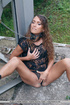 Brunette chained outdoors rubs her cunt on the floor.