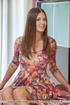 Brunette girl takes off her floral dress on orange…