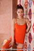 Slim brunette girl in orange body suit and stockings strip naked.
