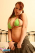 Lusty redhead in white top and green bikini on bed shows big tits and