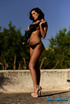 Sizzling hot chick in black bikini and flesh high heels teases with her