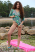 Sexy brunette with long curly hair by the river takes off her clothes