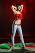 Brunette in jeans and red banduea strip quickly atop the green covers