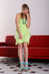 Blonde removes her green dress on a red couch to…