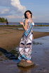 Brunette goddess in a beautiful dress reveals her sexy body by the lake