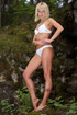 Petite sexy blonde in white lingerie reveals her body in a forest