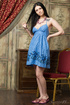 Black haired beauty in blue dress poses atop a dresser exposing herself
