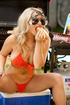 Stunning blonde in tiny red undersized bikini giving a bite to a huge