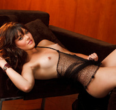 Brunette with beautiful face lays down on the chair wearing black lingerie