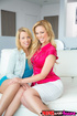 Teen and step-mom enjoy a lesbian tryst on a white sofa before the gal's