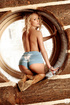 Blonde with long hair poses nude in window wearing cowboy boots