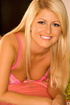 Pleasing blonde in a pink bra and white shorts enjoying while posing on