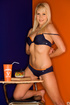 Sporty sexy blonde in orange and blue underwear having a bite in the classroom