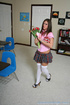 Dangerous brunette schoolgirl in pink uniform and white socks sits on