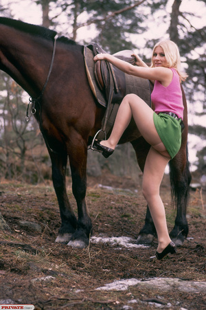 Luscious babe in pink shirt, green skirt, skin tone stockings and black high heels rides on a horse and displays her hot body before she shows her lusty ass in the forest. - XXXonXXX - Pic 2