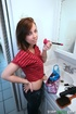 Slender brunette makes up in the bathroom and undressing before blowing