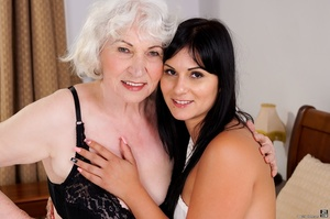 Latina sucks a blonde caucasian granny's tits and pussy in a white hotel room - XXXonXXX - Pic 1