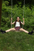 Petite girl plays on the swing outside with a glass dildo stuck in her