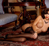 Classy brunette with crimson lips in black stockings and heels lays on