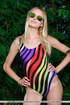Alluring blonde in colorful one piece swimsuit posing her curvy butt enthusiastically