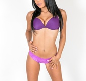 Foxy babe teases with her indulging body in a white room wearing her purple