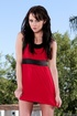 Black haired gal in high heels pulling up her red dress and flashing her