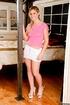 Sexy shaped bimbo in high heels posing tight pink t-shirt and white miniskirt