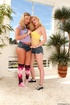 Two blondes in tight jeans shorts posing and kissing each other before