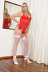 Red peignoir dressed ladyboy posing in white stockings by the mirror and