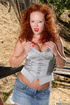 Red lipped redhead with big naturals in grey top pulls up her jeans miniskirt