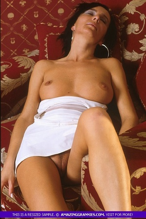 Luscious grandma pose her skinny body outdoor wearing her white dress and black high heels before she goes inside and expose her lusty boobs and nasty pussy in different positions on a maroon couch. - XXXonXXX - Pic 7
