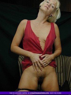 Mature blonde pose her alluring body then pulls down her red blouse and teases with her sweet boobs then peels down her black panty and expose her lusty pussy on a brown couch. - XXXonXXX - Pic 8