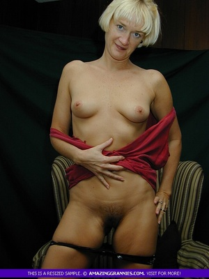 Mature blonde pose her alluring body then pulls down her red blouse and teases with her sweet boobs then peels down her black panty and expose her lusty pussy on a brown couch. - XXXonXXX - Pic 9
