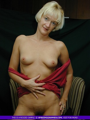 Mature blonde pose her alluring body then pulls down her red blouse and teases with her sweet boobs then peels down her black panty and expose her lusty pussy on a brown couch. - XXXonXXX - Pic 10