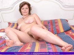 Foxy granny lays naked on a multi colored bed and - XXXonXXX - Pic 4