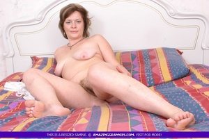 Foxy granny lays naked on a multi colored bed and displays her fat body with indulging boobs and hairy pussy. - XXXonXXX - Pic 4