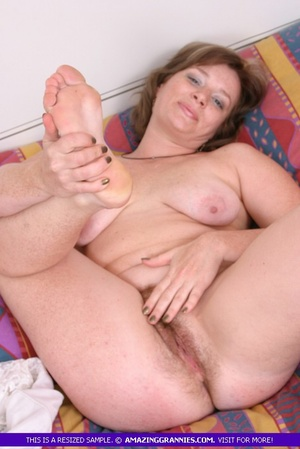 Foxy granny lays naked on a multi colored bed and displays her fat body with indulging boobs and hairy pussy. - XXXonXXX - Pic 12