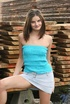 Hunky brunette wearing teal top and denim light skirt celebrates her sexuality
