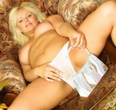Steaming hot blonde sits topless on a brown couch and expose her indulging