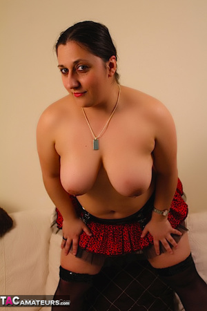 Cute BBW reveals her large breasts in red and black dress and black stockings then gets naked and expose her indulging twat as she opens her legs wide on a white couch. - XXXonXXX - Pic 9