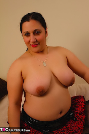 Cute BBW reveals her large breasts in red and black dress and black stockings then gets naked and expose her indulging twat as she opens her legs wide on a white couch. - XXXonXXX - Pic 11