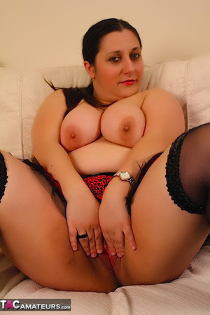 Cute BBW reveals her large breasts in red and black dress and black stockings then gets naked and expose her indulging twat as she opens her legs wide on a white couch. - XXXonXXX - Pic 17